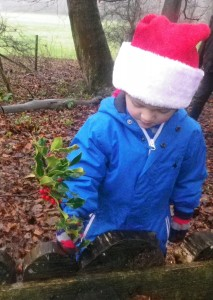 Decorating the Mud Kitchen with holly.